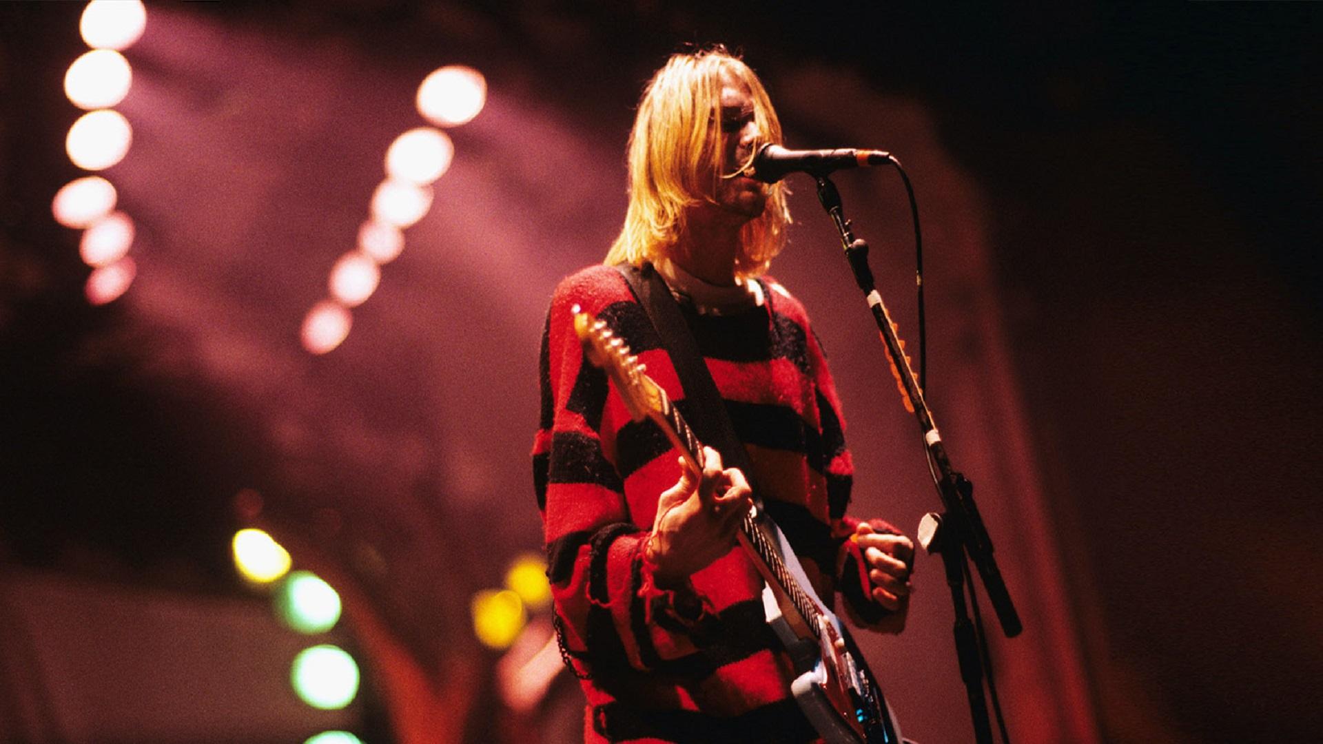 El frontman Kurt Cobain cantando en un concierto con luces rojas